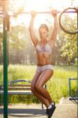 Sexy young fitness girl pulls up on street sport gym. Brunette fitness woman in sport wear with perfect fitness body on street workout performing abdominal exercises on the horizontal bar — Stockfoto