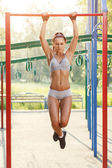 Sexy young fitness girl pulls up on street sport gym. Brunette fitness woman in sport wear with perfect fitness body on street workout performing abdominal exercises on the horizontal bar — Stock Photo