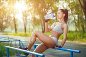 Fitness woman relax after workout exercises on parallel bars outdoor with shaker bottle of water. brunette fit girl relax after street training — Stock Photo