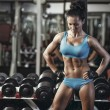 Sexy young girl resting after dumbbells exercises. Fitness woman in blue sport wear with perfect fitness body resting in gym — Stock Photo #52940149