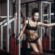 Sexy young girl in the gym holding on training machine. Brunette fitness woman in black sport wear with perfect fitness body in gym — Stock Photo #52940219