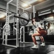 Young sexy girl in the gym doing squat with barbell — Stock Photo #52940387