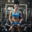 Young sexy brunette girl in the gym doing biceps exercise with barbell — Stock Photo #52940555