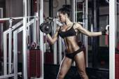 Fitness woman doing exercises with dumbbell in the gym. Brunette fitness girl in black sport wear with perfect body performing biceps exercises — Stock Photo