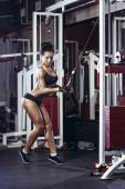 Fitness woman doing triceps exercises in the gym. Brunette fitness girl in black sport wear with perfect body in gym exercising — Stock Photo