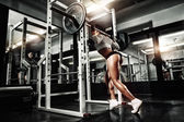 Young sexy girl in the gym doing squat with barbell — Stock Photo