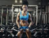 Young sexy brunette girl in the gym doing biceps exercise with barbell — Stockfoto