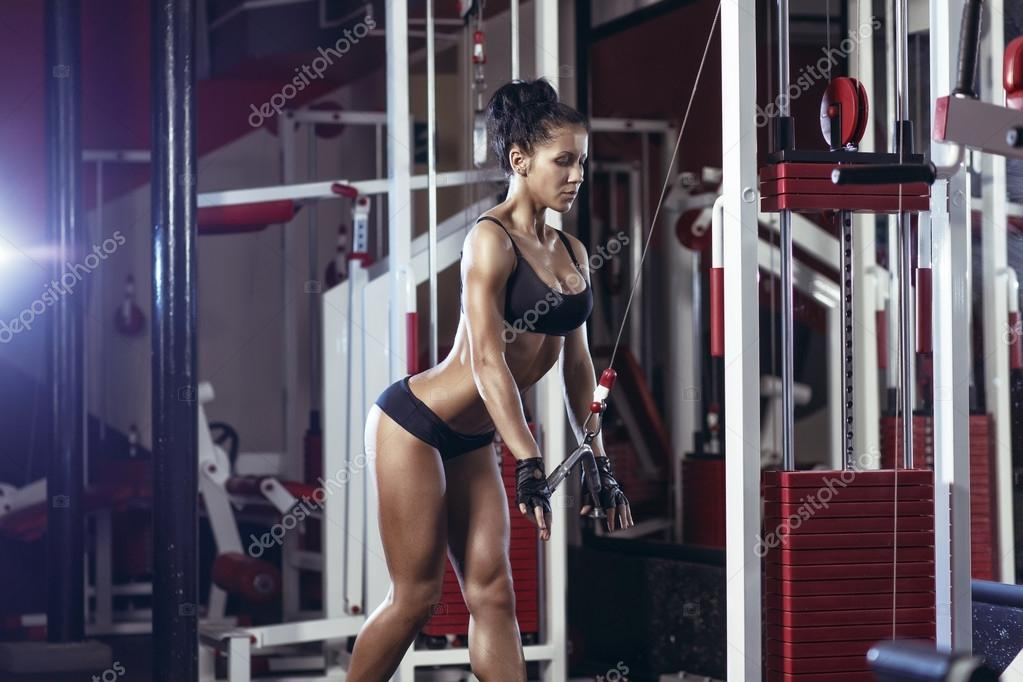 Fitness woman doing triceps exercises in the gym. Brunette fitness ...