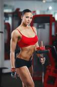 Fitness body girl with barbell in the gym — Stock Photo