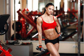 Girl with perfect body with dumbbells in the gym — Zdjęcie stockowe