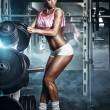 Athletic young sexy blonde girl sets weight on barbell in the gym — Stock fotografie #53590567