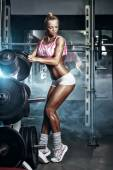 Athletic young sexy blonde girl sets weight on barbell in the gym — Stock Photo