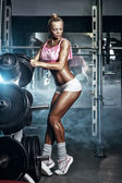 Athletic young sexy blonde girl sets weight on barbell in the gym — Stock fotografie