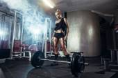 Fitness blonde girl prepares for exercising with barbell in gym — Stock Photo