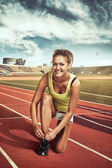 Female runner tying lace on stadium — Stockfoto