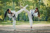 Gemini girl karate crossed their legs in the air outdoors — Стоковое фото