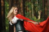 Portrait of a blonde lady in old-fashioned dress and red cloak in a fairy forest — Stock Photo