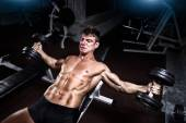 Athlete in the gym training with dumbbells — ストック写真