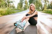Young woman in the rollerblades, sitting on road in outdoor — Foto Stock