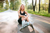 Young woman in the rollerblades, sitting on road in outdoor — Stockfoto