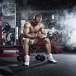 Very power athletic guy, relaxing after workout in sport hall — Stock Photo #55739895