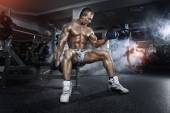 Athlete in the gym training with dumbbells — Stock Photo