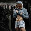Bodybuilder girl showing her abdominal muscles — Stock Photo #55742243