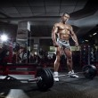 Very power athletic guy standing with barbell, workout in sport — Stock Photo #55760365