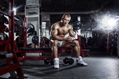 Very power athletic guy, relaxing after workout in sport hall  — Stock Photo