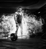 Very power athletic guy standing with barbell, workout in sport — Stock Photo