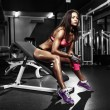 Fitness girl with shaker posing on bench in the gym — Stock Photo #59438107