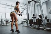 Sexy athlete woman posing with simulator in the gym — Stock Photo
