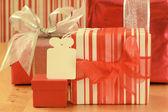 Gift in red and white striped wrapping paper with empty white gift tag — Stock Photo