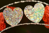 Close up of two silver sparkly flat foil hearts on black background — Stock Photo