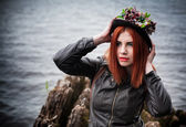A beautiful Russian redhead girl sitting on the beach and looking into the distance — Stock Photo