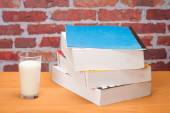 Book for school with glass of milk — Stock Photo