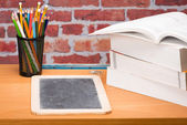Desk with school supplies and slate — Stock Photo