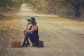 Girl with luggage in vintage style — Stock Photo