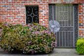 Flowers on a background a brick house — Stock Photo