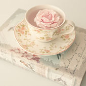 Rose in cup of tea on the book — Foto Stock