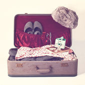 Suitcase with clothes and camera — Stockfoto