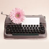 Typewriter and flower on table — Stock Photo
