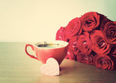 Red roses and cup of coffee — Stock Photo