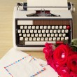 Vintage typewriter and bouquet of roses — Stock Photo #63102215