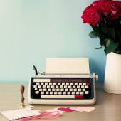 Vintage typewriter and bouquet of roses — Stock fotografie
