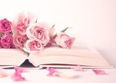 Pink peonies and roses on book — Stock Photo