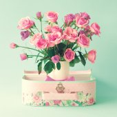 Pink roses in vase in retro suitcase — Stock Photo