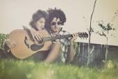 Boy teaches girl to play guitar — Stock Photo