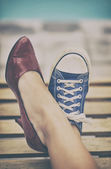 Woman legs in different shoes — Stock Photo