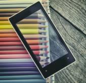 Mobile phone on colorful pencils — Stockfoto